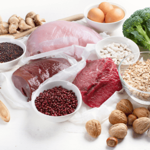Main image for the article [Everything to know about iron and your baby]. Pictured are high iron foods including: beef, liver, chicken, broccoli, nuts, beans and oatmeal.