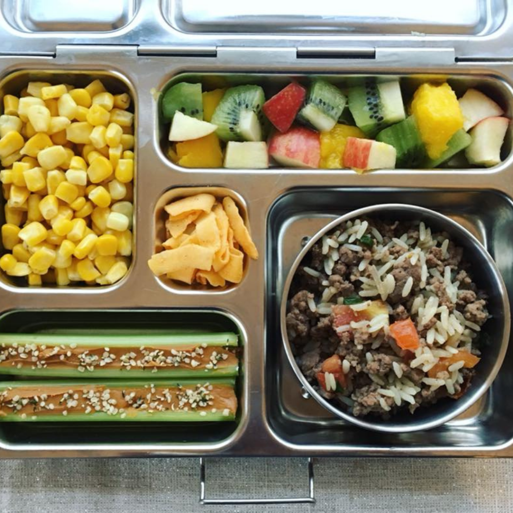 Main image for the article [The Ultimate Lunch Packing Guide]. Pictured is an open lunchbox with mixed fruit, corn, rice, hamburger and tomatoes, and celery with peanut butter on top.