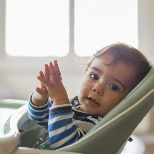 baby leaning on high chair tray