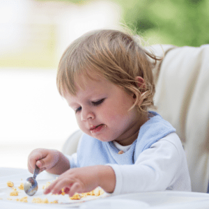 Main image for the article [My baby barely eats...is this normal?]. Pictured is a baby eating food from their highchair tray.