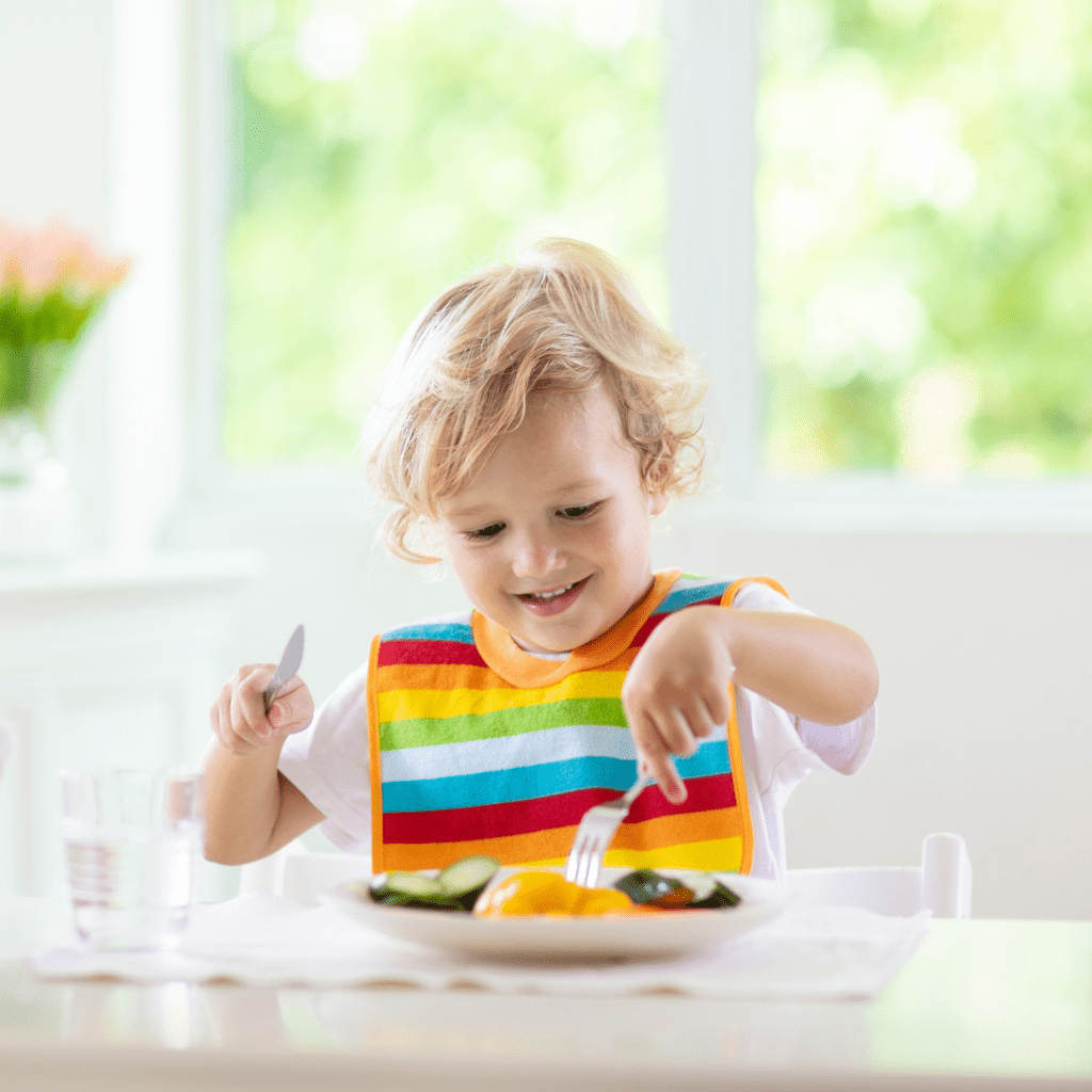 Main image for the article [The Most Likeable Veggie Dishes For Kids]. Pictured is a toddler eating a plate of vegetables.