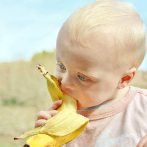 Main image for the article [Baby Led Feeding Travel Food Ideas]. Pictured is a baby sitting outside and eating a banana.