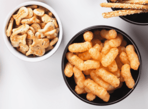 Main image for the article [Salt for babies: How much is too much?. Pictured is a bowl of goldfish crackers, pretzel sticks and a bowl of cheese puffs.