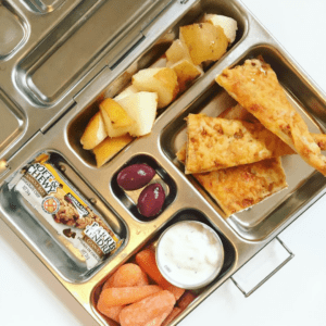 Main image for the article [How a simple mindset shift can remove the stress from lunch packing]. Pictured is lunchbox with homemade pizza, carrots and dip, olives, pears and a granola bar.