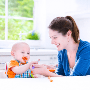 Main image for the article [When is the right time to start solids?]. Pictured is a mother helping her baby eat from a spoon.