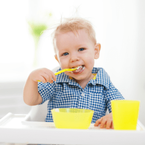 Main image for the article [How to teach mindful eating to your toddler]. Pictured is a toddler sitting at a table eating yogurt with a spoon.