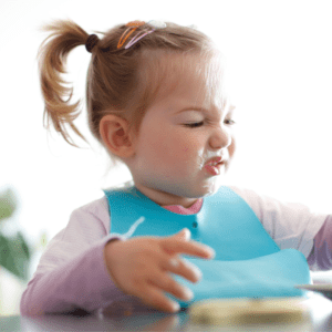 """Main image for the article [Avoiding Food Ruts With The """"Rotation Rule"""" ]. Pictured is a toddler sitting at the table and making a disgusted face at her food."""