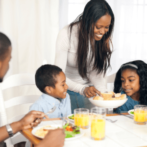 Main image for the article [Why And How To Start Serving Family Style Meals]. Pictured is a family eating salad and rolls together.