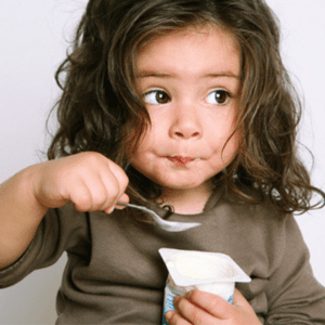 Main image for the article [The Best Yogurts For Your Baby]. Pictured is toddler eating a yogurt cup with a spoon.