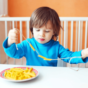 Main image for the article [How to Use Food Exploration to Ease Picky Eating]. Pictured is toddler threading a string with noodles.