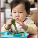 infant in high chair holding broccoli ready to eat using baby led weaning method