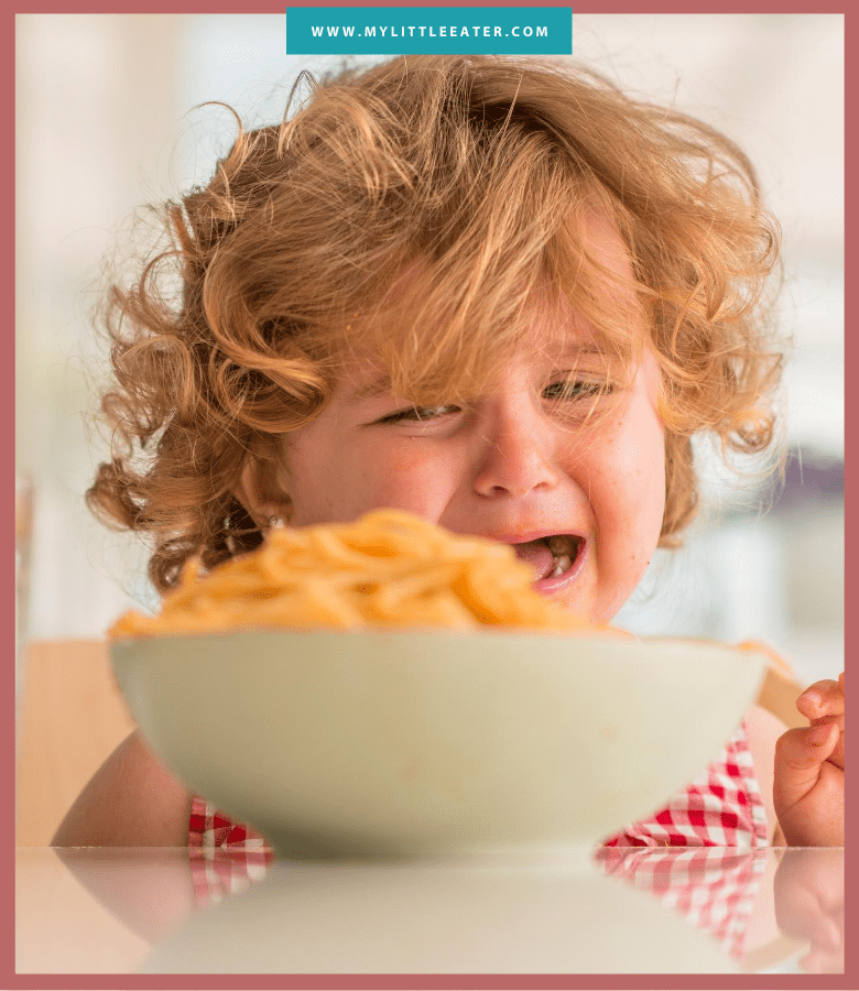 white toddler with blond curly hair crying at a table with a bowl of noodles on it