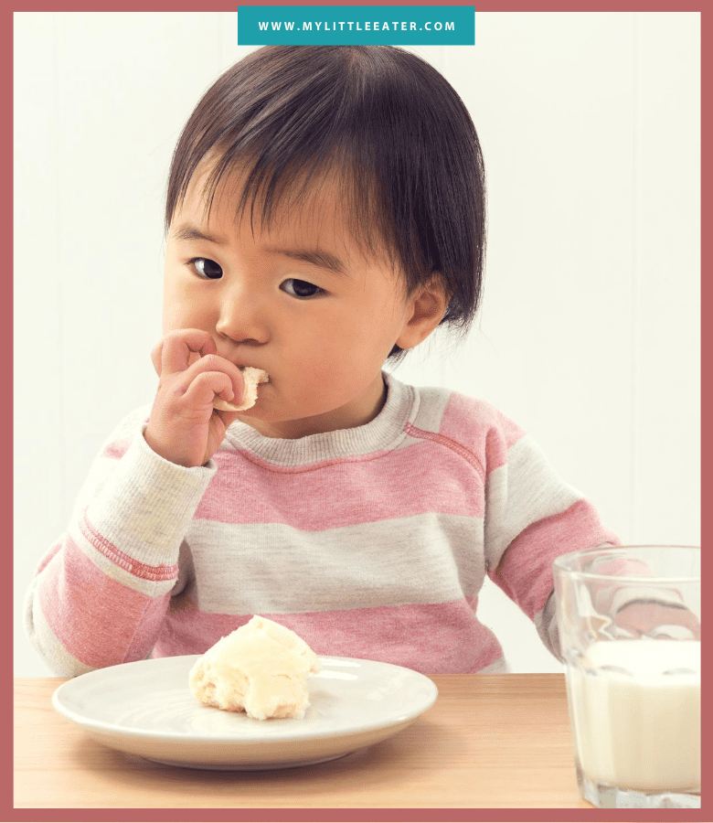toddler in a pink and white striped sweater eating a dinner roll; half is still on the plate, and a glass of milk beside it on the table
