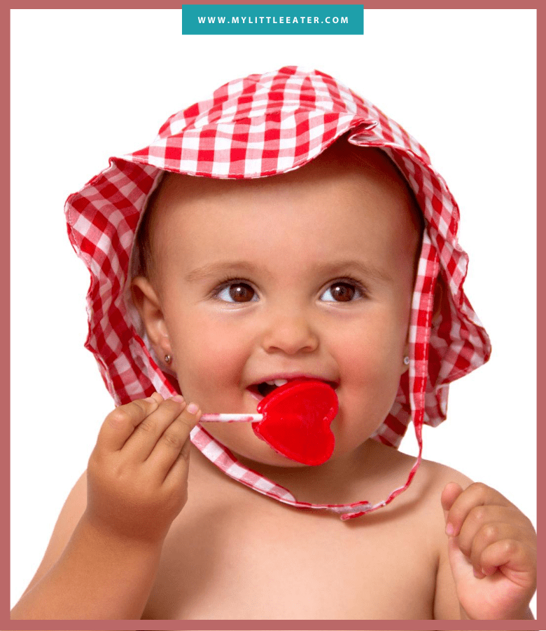 white baby in red sunhat eating a heart shaped lollipop