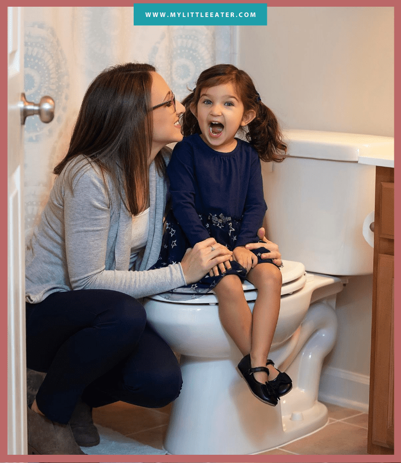 a mom squats down beside her daughter who is sitting on a toilet with a big smile on her face