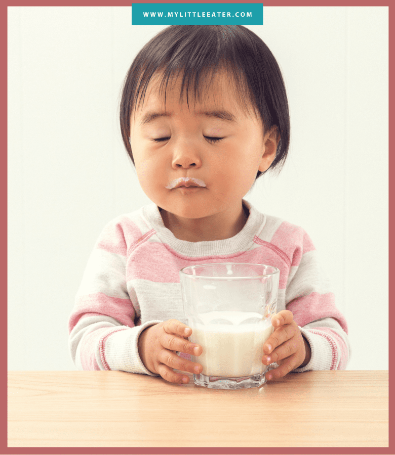 "A toddler sits at a table with her eyes closed, holding a glass of milk. The toddler has a ""milk moustache"" from drinking the milk. Image has a maroon border, and the website ""mylittleeater.com"" is printed at the top in white font on a aqua background."