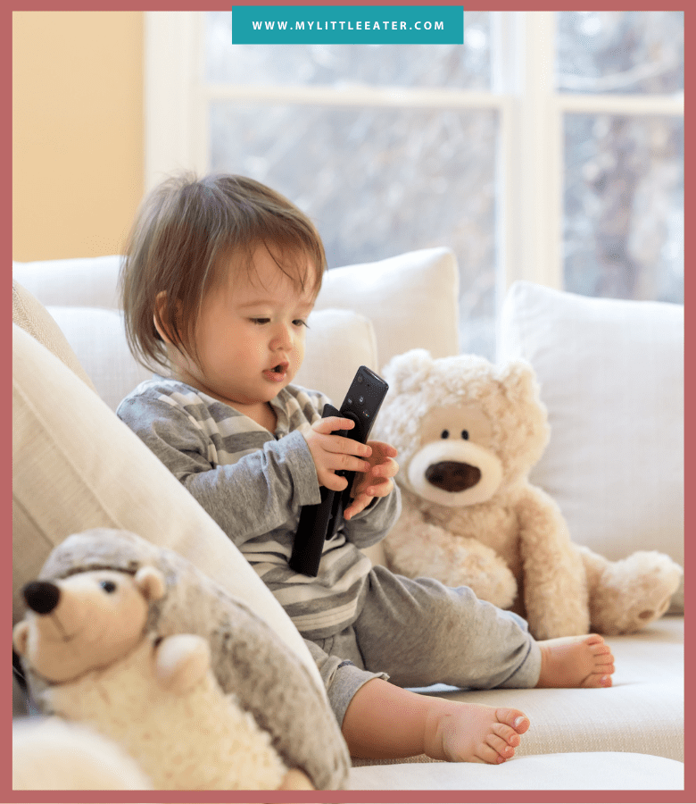 "Episode art for ""#31: Screen Time and Other Distractions During Meals"", a baby sits on a couch with two stuffed animals, holding a TV remote."
