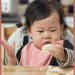 """Episode art for episode """"#43: The Best Bread for Baby Led Feeding."""" Pictured is a baby sitting in a high chair looking at a piece of bread."""