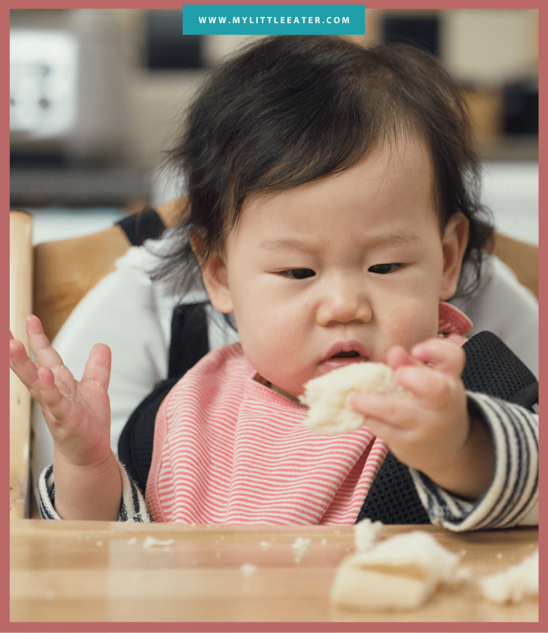 "Episode art for episode ""#43: The Best Bread for Baby Led Feeding."" Pictured is a baby sitting in a high chair looking at a piece of bread."