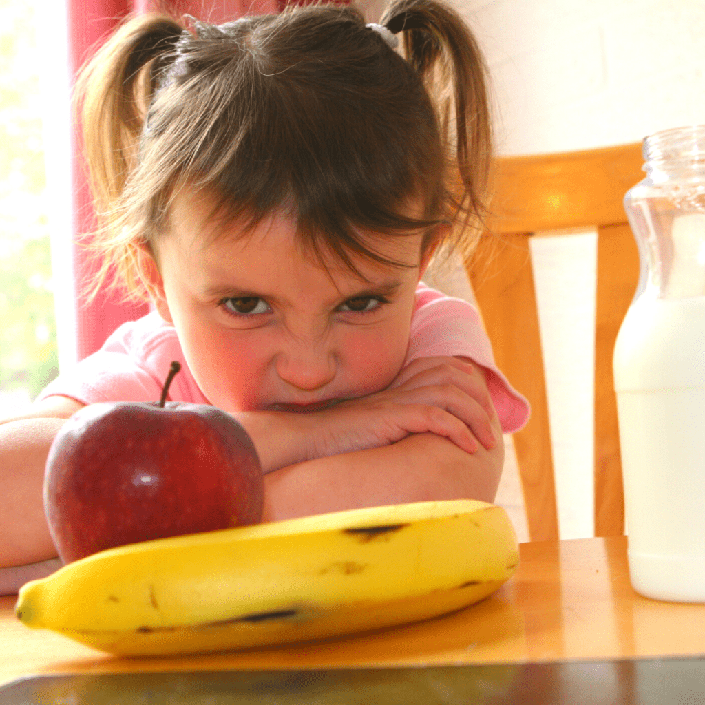 """Main image for the article: """"When picky eating moves from normal to extreme"""". Pictured is a toddler at the table looking unhappy with an apple, banana, and milk in front of them."""