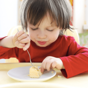 "Episode art for episode ""#47:Everything to know about eggs for your baby & toddler."" Pictured is a toddler eating scrambled eggs."
