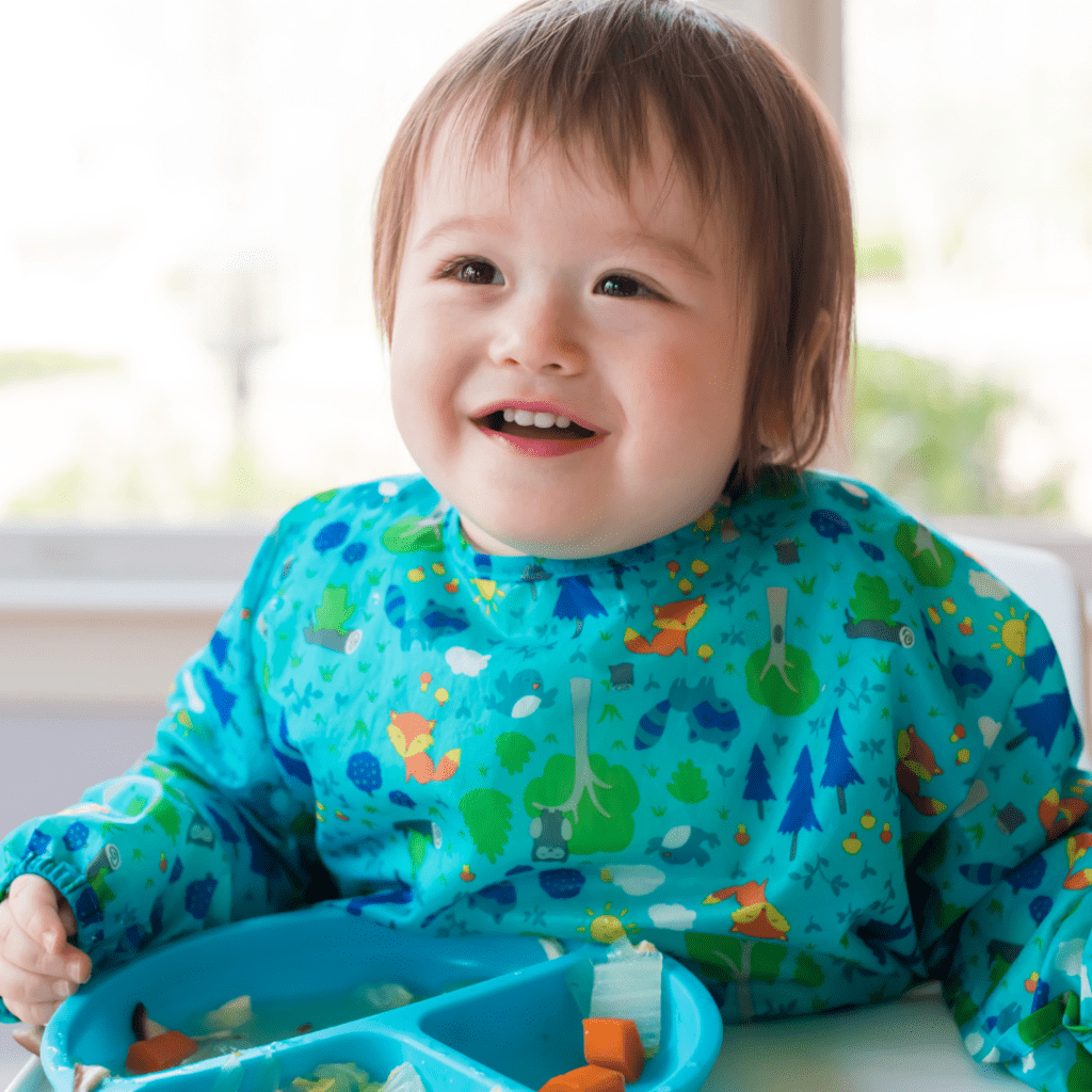 Main image for the article [What is toddler led feeding?]. Pictured is a baby sitting in a highchair, eating carrots with a fork.