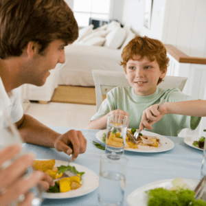 """Main image for article """"The importance of timing for preventing (and reversing) picky eating."""" Pictured is a family happily eating dinner together."""