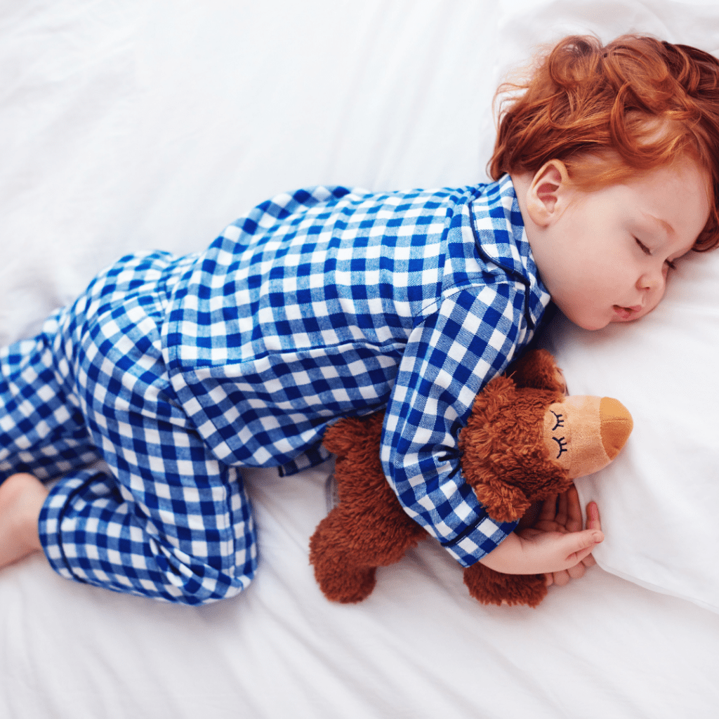 """Main image for the article """"Common Toddler Sleep Problems and How You Can Manage Them"""". Pictured is a sleeping toddler cuddling their teddy bear."""
