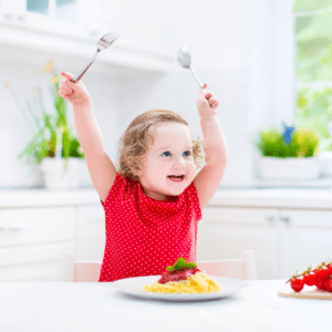 "Featured image for article: ""Limiting Food: Is it ever okay to control how much your toddler eats?"". Pictured is a smiling toddler at a table with a plate of spaghetti in front of them."