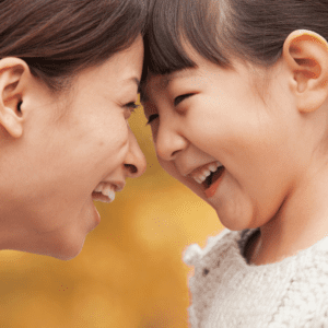 "Featured image for the article ""Parenting styles: What authoritative parenting is and why it's recommended."" Pictured is a mother and daughter smiling at each other, face-to-face."