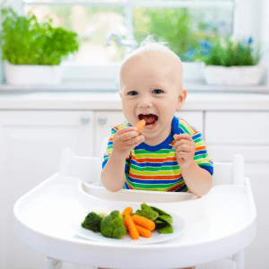 "Featured image for article: ""Choking prevention and when food modifications are no longer needed"". Pictured is a baby eating a baby carrot."
