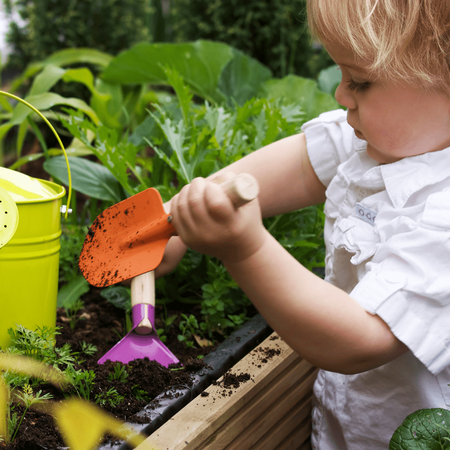 "Featured image for the article: ""Top Tips for Gardening with Kids"". Pictured is a toddler digging in a garden."
