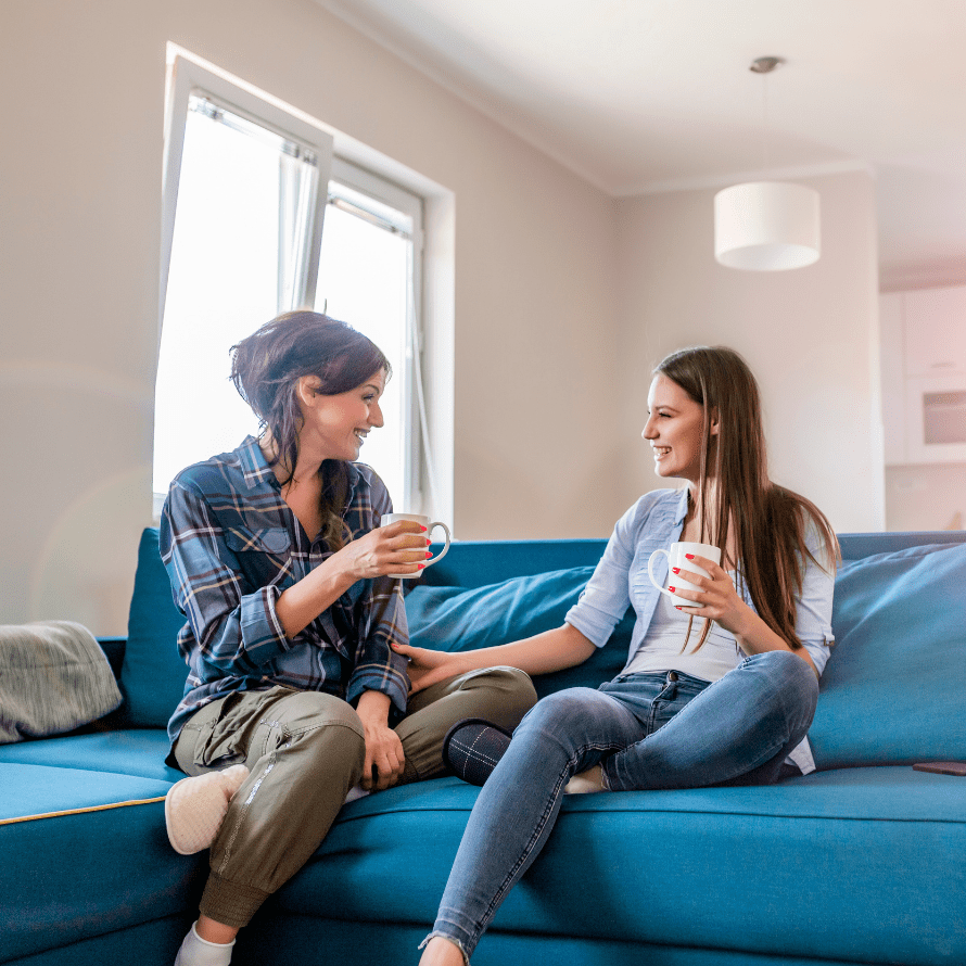 """Featured image for the article: """"Top tips from a friendship coach on making and maintaining friendships as a mom."""" Pictured is two friends chatting while having coffee."""