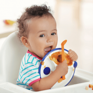 """Episode art for episode: """"#65: Plates for babies & toddlers: What age to use them, divided or not, and my favourite plate recommendations"""". Pictured is a baby holding their plate in their high chair."""