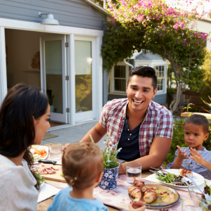 """Episode art for episode: """"#70:What to say to toddlers to get them to eat (without pressure!)"""". Pictured is a man and woman talking to their children during meal time."""