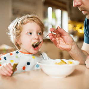 """Episode art for episode: """"#72: Help! My toddler won't feed themselves!"""" Pictured is a toddler being fed by a parent."""