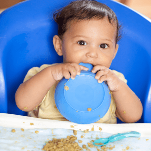 """Episode art for episode: """"#73: How to serve lentils to babies and toddlers ."""" Pictured is a baby holding a bowl close to their mouth with lentils on their tray."""