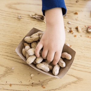 """Featured image for article: """"Top Tips for safely serving peanuts to babies and toddlers"""". Pictured is a child's hand reaching for some peanuts."""
