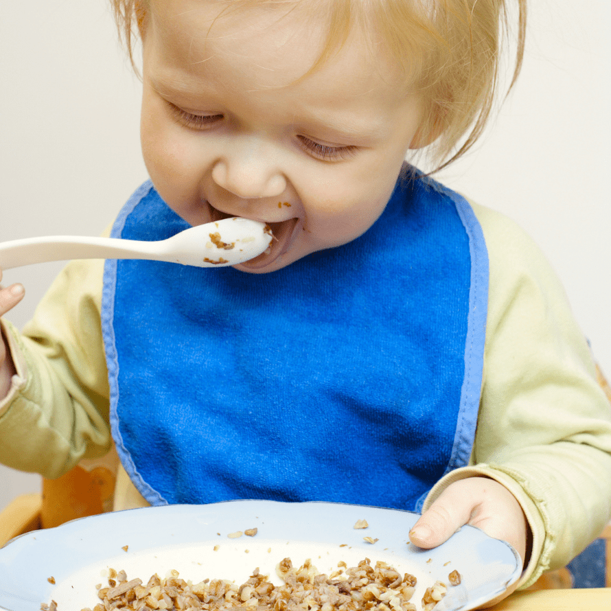 """Featured image for article: """"The truth about serving grains and other starches to your baby"""". Pictured is a baby eating a bowl of oatmeal."""