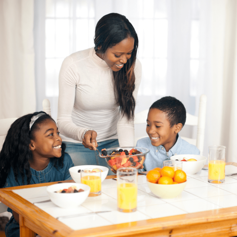 """Featured image for article: """"Proven phrases for getting your toddler to eat - without pressure or bribes!"""". Pictured is a mom serving her two children fruit."""