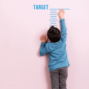 Child reaching to top of growth chart on wall